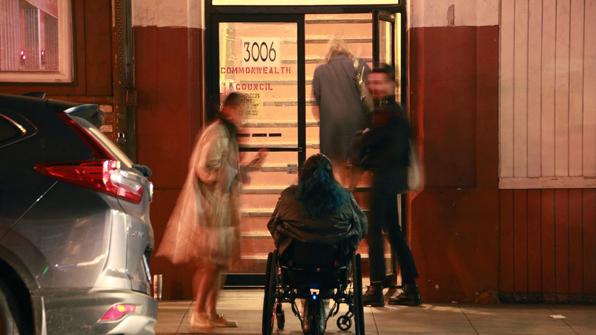 """Jaklin Romine sitting in her wheelchair in front stairway and a glass door. Still from video performance at Los Angeles Contemporary Archive of """"Access Denied"""" by Jaklin Romine, 2015. 