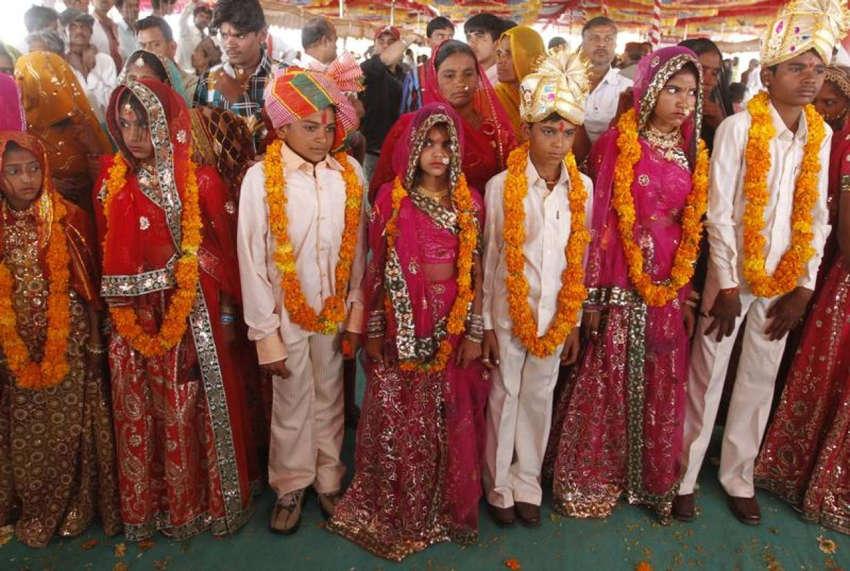 Boys and girls from the Saraniya community wearing garlands pose for pictures after their engagement ceremony at Vadia village in the western Indian state of Gujarat March 11, 2012. | REUTERS/Amit Dave