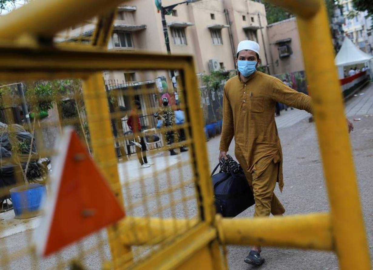 A man wearing a protective mask walks to board a bus that will take him to a quarantine facility, amid concerns about the spread of coronavirus disease (COVID-19), in Nizamuddin area of New Delhi, India, March 30, 2020. | REUTERS/Danish Siddiqui