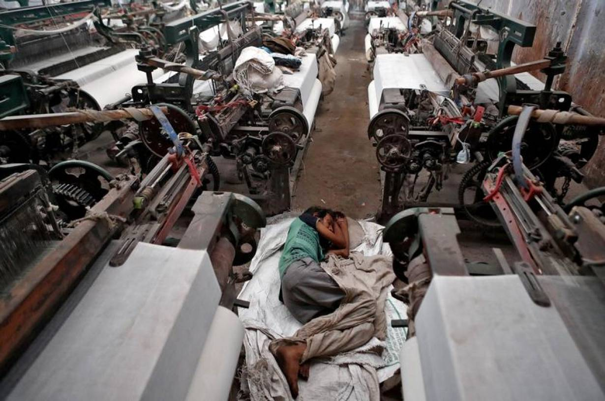 A migrant worker, who works in a textile loom, rests inside a loom after it was shut due to the 21-day nationwide lockdown to slow the spread of the coronavirus disease on the outskirts of Mumbai, India, April 1, 2020. | REUTERS/Francis Mascarenhas