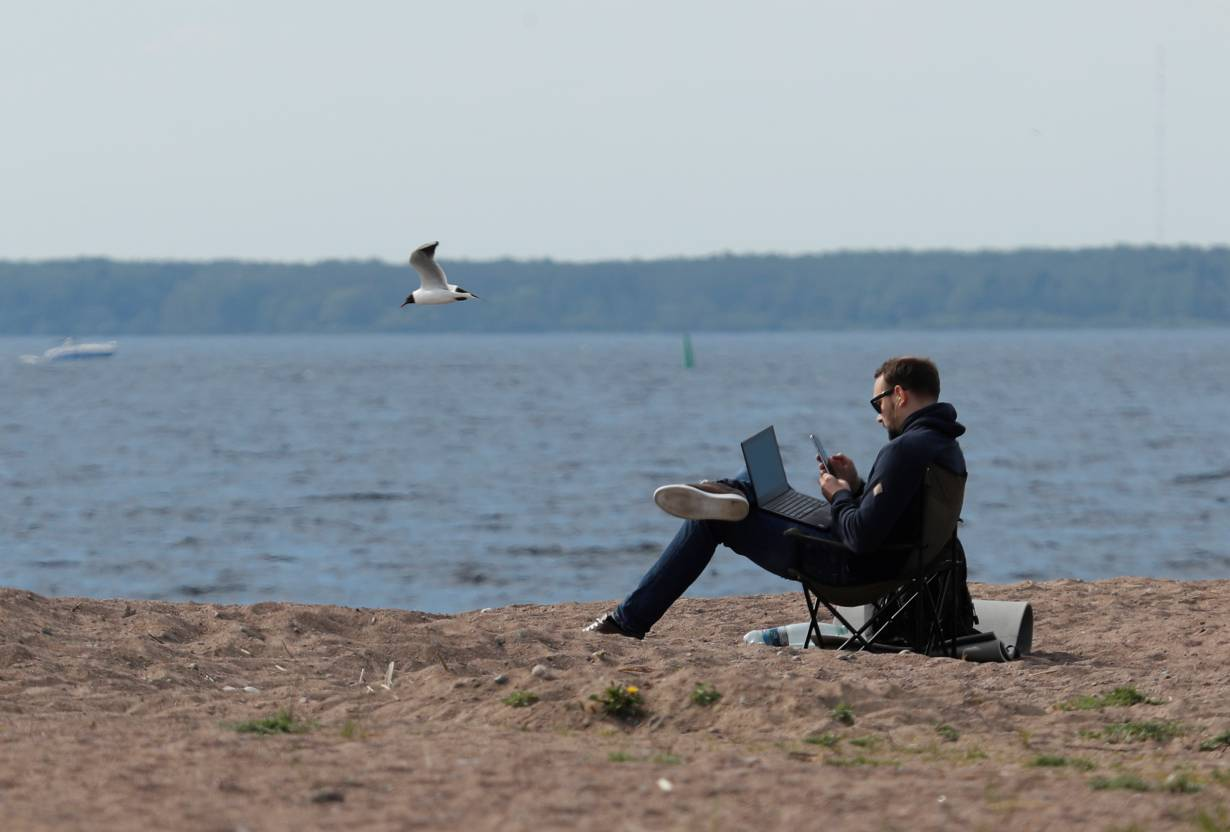 FILE PHOTO: A man uses his smartphone and laptop as he sits on the shore of the Gulf of Finland amid the outbreak of the coronavirus disease (COVID-19) in Saint Petersburg, Russia May 27, 2020. | REUTERS/Anton Vaganov