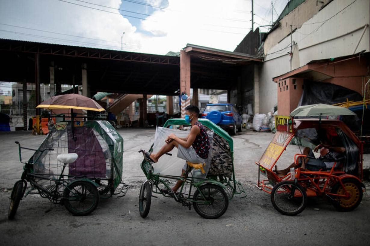 Rickshaws lined with plastic as a makeshift protective measure against the coronavirus disease (COVID-19) are parked on a sidewalk as they wait for passengers, in Manila, Philippines, May 28, 2020. | REUTERS/Eloisa Lopez