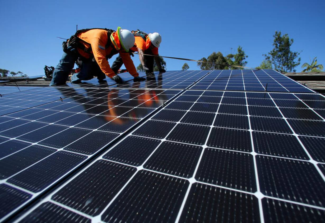 ILE PHOTO: Solar installers from Baker Electric place solar panels on the roof of a residential home in Scripps Ranch, San Diego, California, U.S. October 14, 2016. Picture taken October 14, 2016.   REUTERS/Mike Blake/File Photo