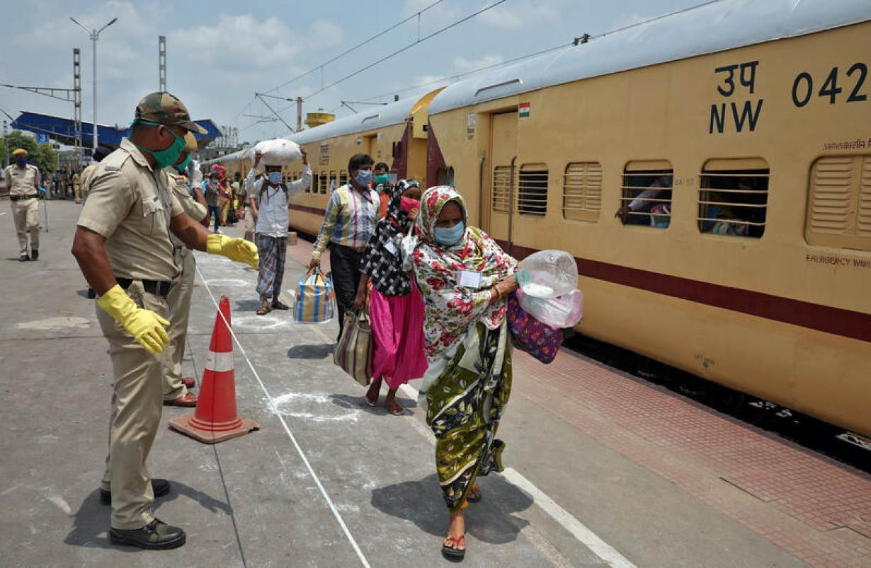 FILE PHOTO: Migrant workers and pilgrims, who were stranded in the western state of Rajasthan due to a lockdown imposed by the government to prevent the spread of coronavirus disease (COVID-19), carry their belongings after their arrival in their state