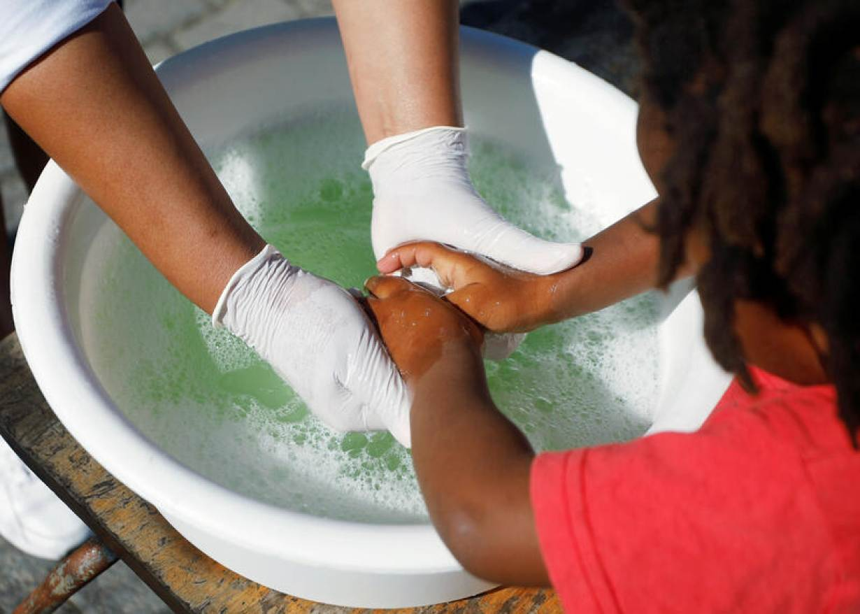 A volunteer helps a child wash her hands at a school feeding scheme during a nationwide lockdown aimed at limiting the spread of the coronavirus disease (COVID-19) in Blue Downs township near Cape Town, South Africa, May 4, 2020. Picture taken May 4, 2020