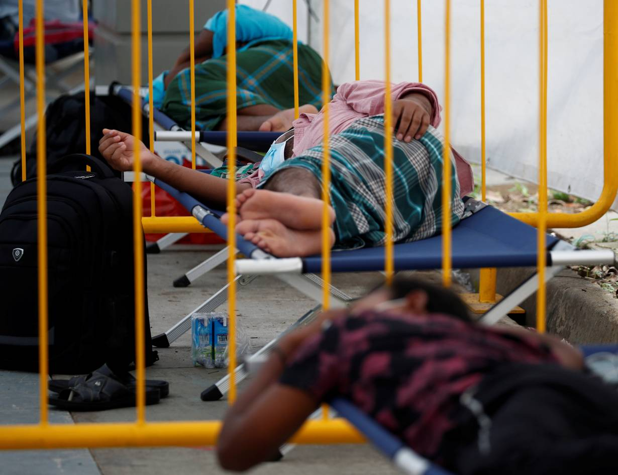 FILE PHOTO: Migrant workers rest at a swab isolation facility as they wait for their test results at a dormitory, amid the coronavirus disease (COVID-19) outbreak in Singapore May 15, 2020.   REUTERS/Edgar Su/File Photo