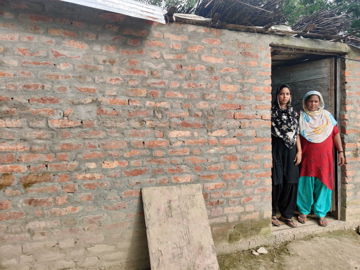 Mantasha Bano (L) stands with her mother-in-law (R) at doorway of their shanty in Atesua village, India on August 26, 2020.   Thomson Reuters Foundation/Saurabh Sharma