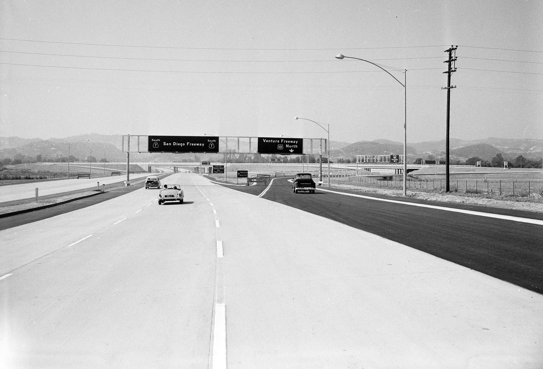 The concrete practically glistens in this 1958 photograph of the San Diego Freeway (then CA-7, now I-405), looking south at its junction with the Ventura Freeway, courtesy of the Los Angeles Examiner collection, USC Libraries