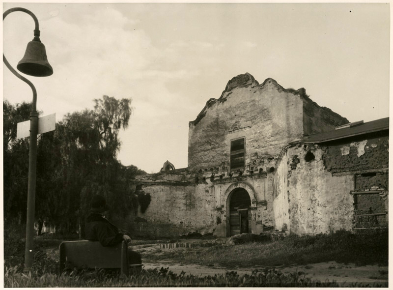An El Camino Real bell stands outside Mission San Diego in 1930