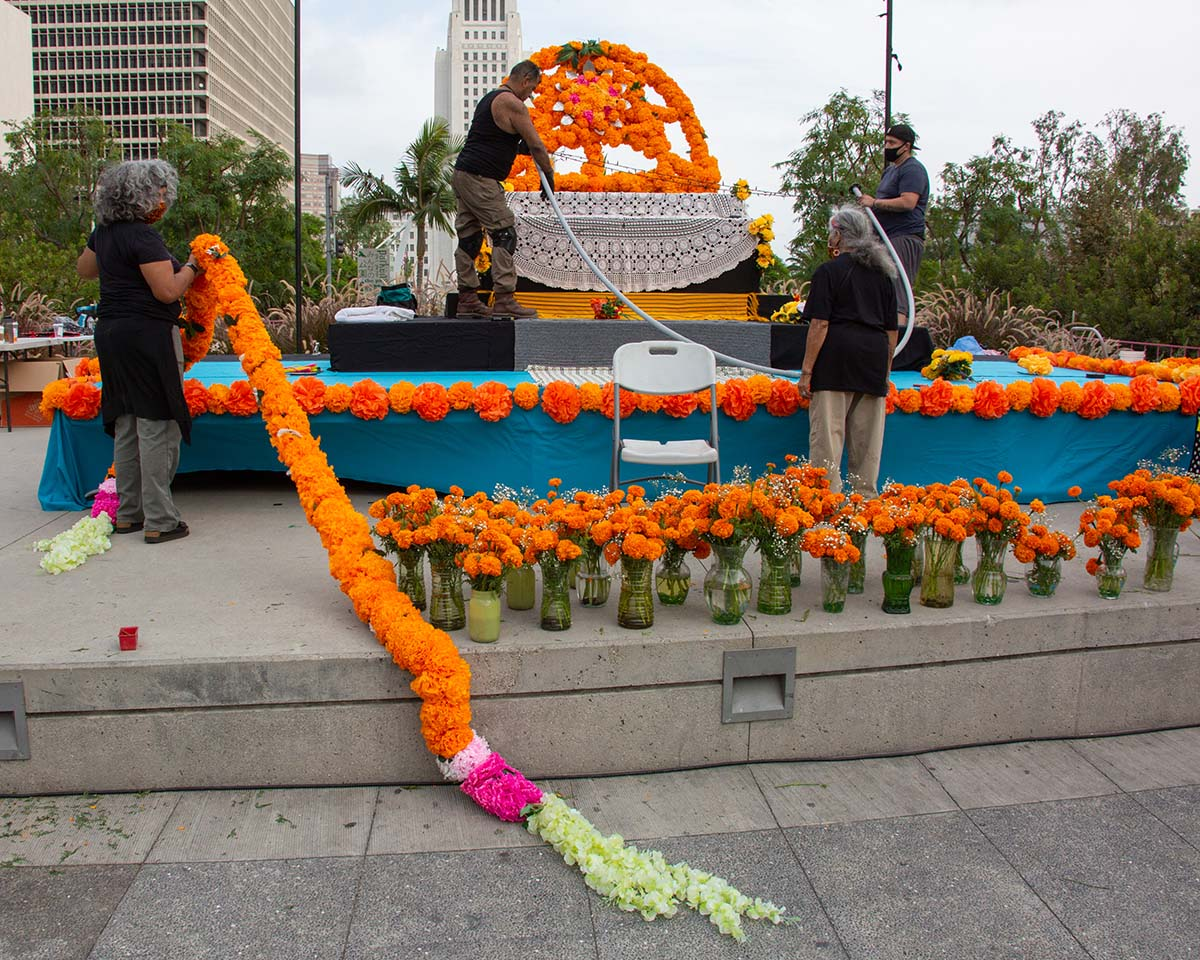 People working on putting up decorations on an ofrenda for Día de los Muertos 2020 | Rafael Cardenas at Grand Park