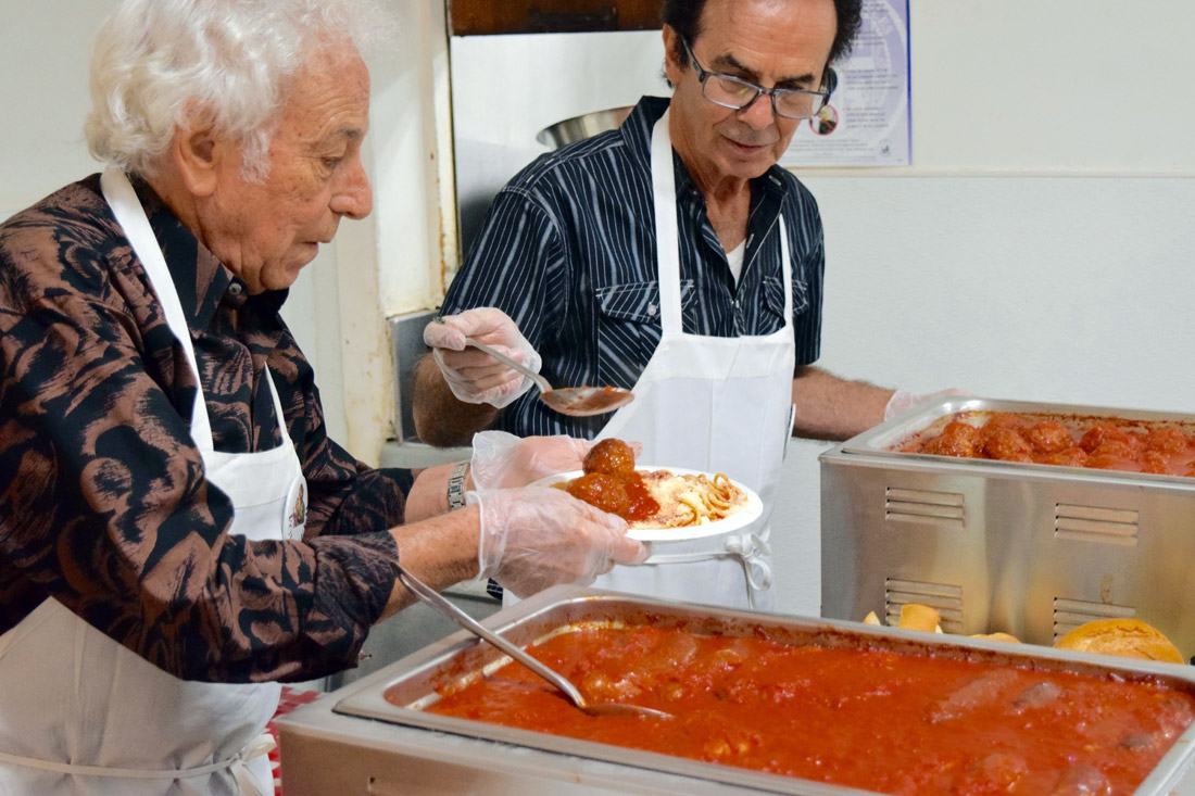 Volunteers serve meatballs and sausages for the feast, St. Joseph's Table