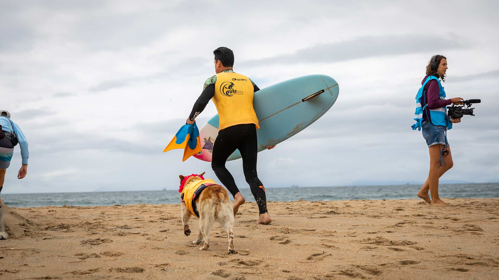Surfer in yellow runs on the beach sand with his dog at his side