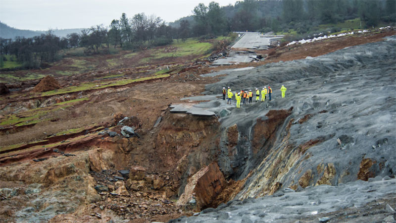 Workers survey erosion of the emergency spillway at Oroville Dam. | Florence Low / California Department of Water Resources