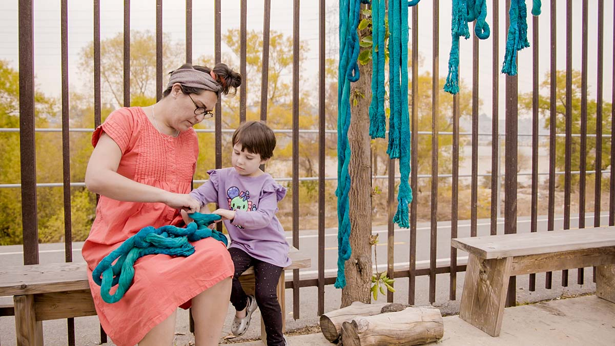 "Artist Tanya Aguiñiga with her child, Io | Still from KCET Artbound's ""Artist and Mother"" Mother AB s9"