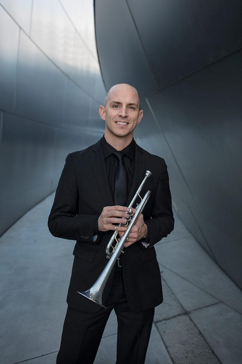 Tom Hooten poses holding his trumpet. | Ryan Hunter