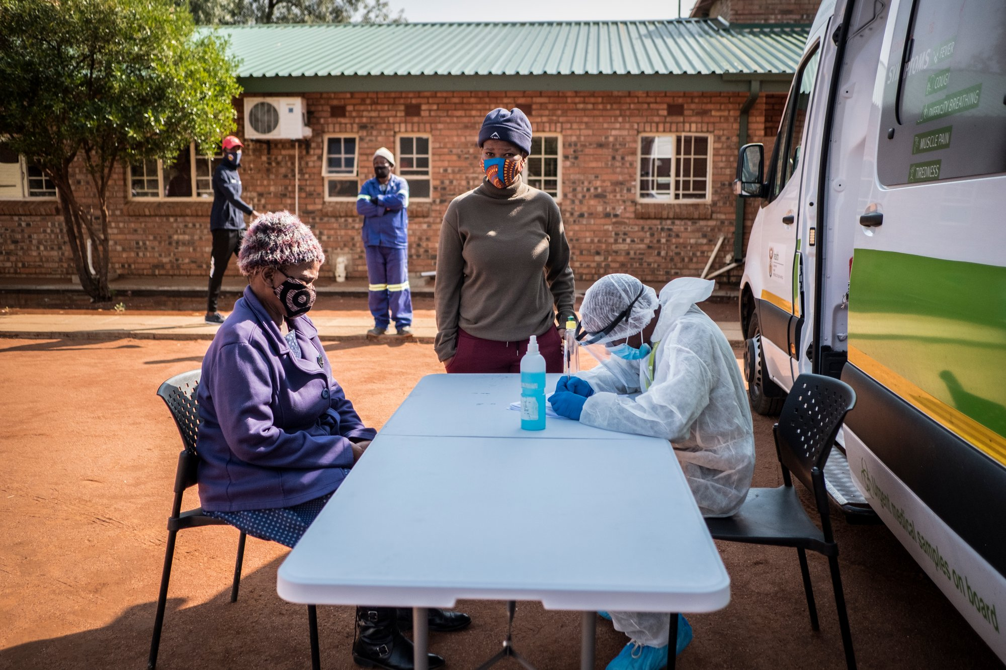 A nurse wearing PPE assess a masked person sitting in front as another masked person looks on.   Thomson Reuters Foundation