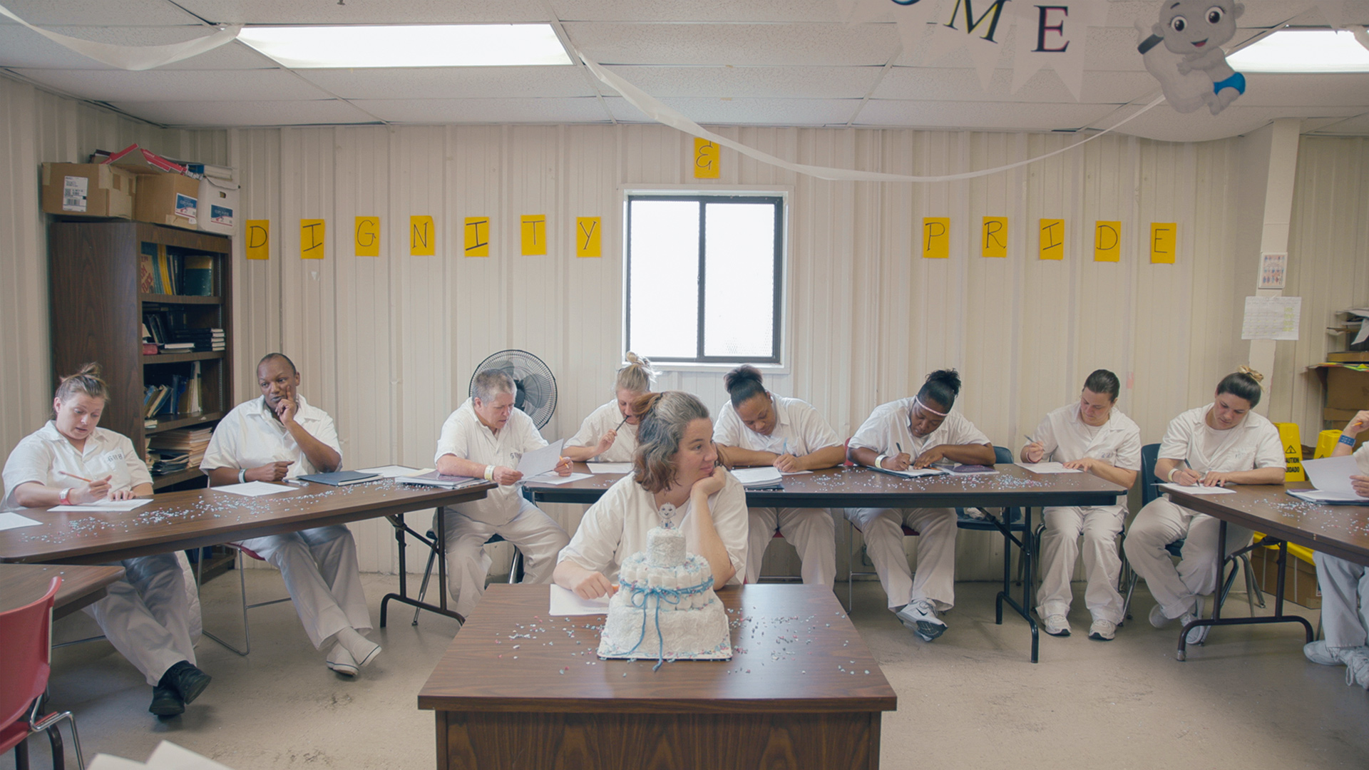"""Pregnant inmate Misty sits in the center of a room with a cake celebrating her soon newborn baby in front of her, with fellow inmates sitting around her writing on pieces of paper. 