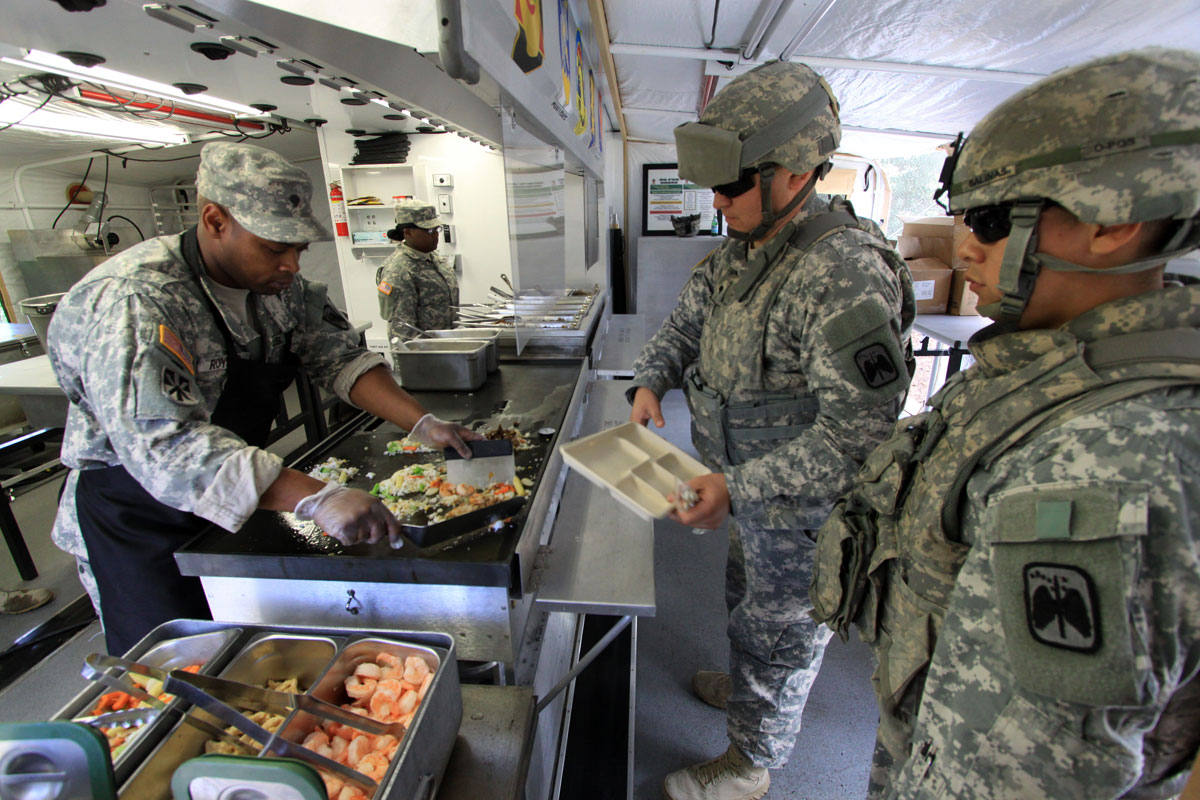 U.S. Army Spc. Michael Royster, a cook assigned to the 46th Aviation Support Battalion (ASB), serves food inside the 16th Combat Aviation Brigade containerized kitchen to 46th ASB Soldiers during the field | Wikimedia Commons
