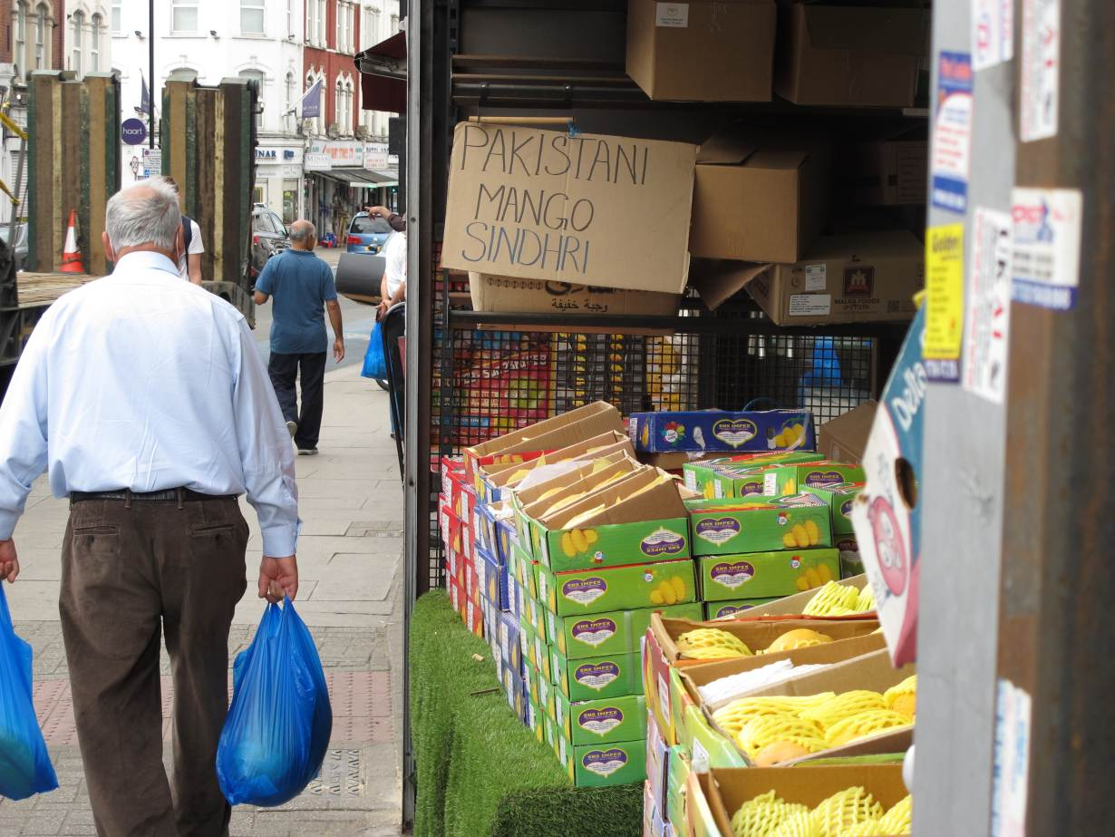 A resident passes a display of Pakistani mangoes for sale in the Tooting neighborhood of London, June 15, 2020. | Thomson Reuters Foundation/Laurie Goering