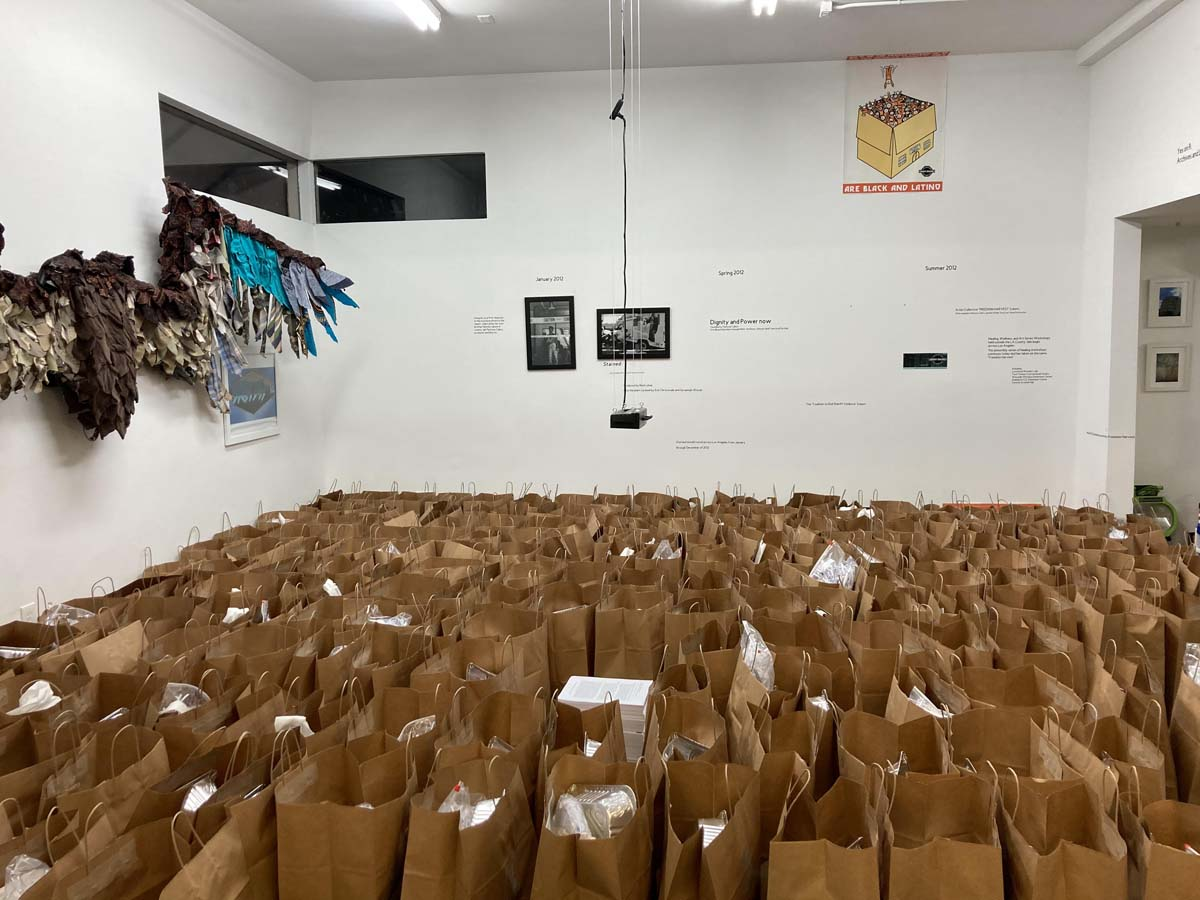 The art supply kits going to high schoolers, packaged in brown paper bags, fill the space at Crenshaw Dairy Mart | Jake Freilich, Ducle Soledad Ibarra and Ana Briz prepare the art supply kits for high schoolers | Courtesy of Crenshaw Dairy Mart