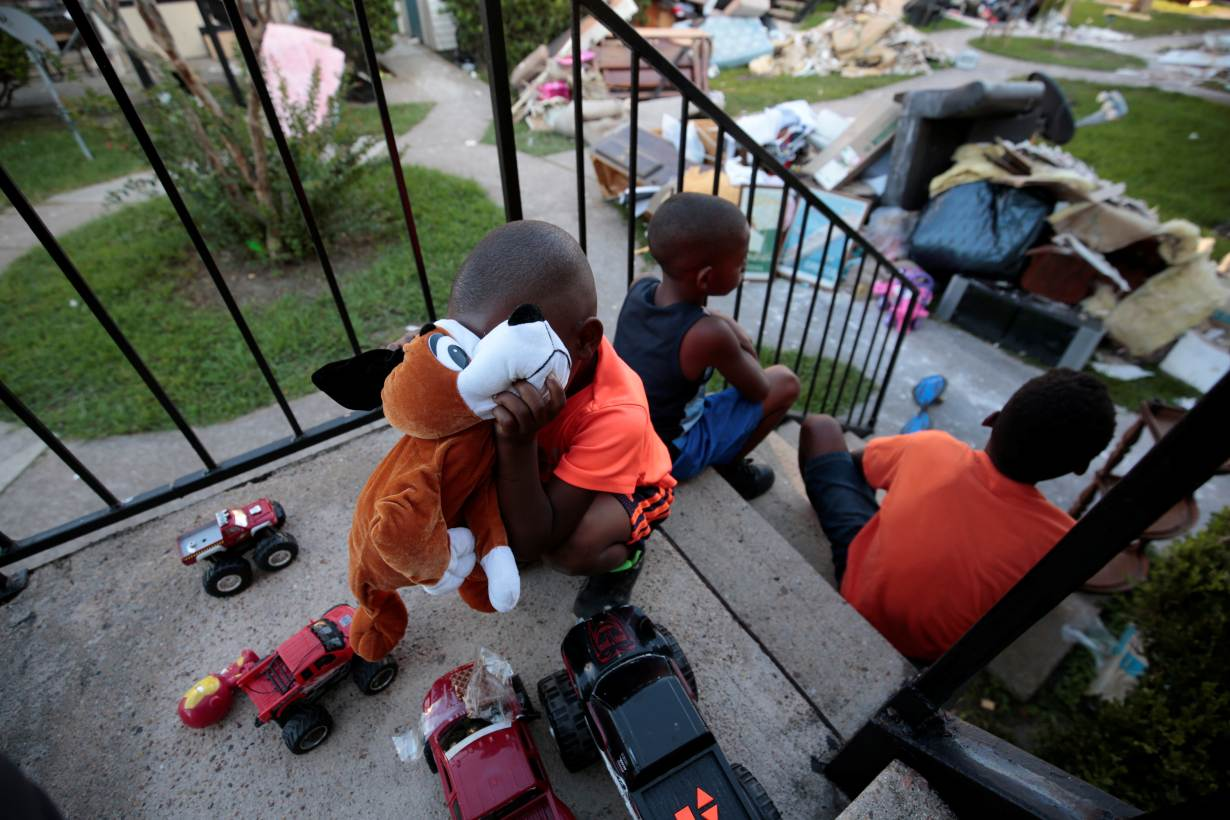 ARCHIVE PHOTO: From left, Kameron Smith, 4, Darius Smith, 9, and Deandre Green, 10, play with toys that they found in the piles of destroyed property at Crofton Place Apartments in the aftermath of Hurricane Harvey in Houston, Texas.