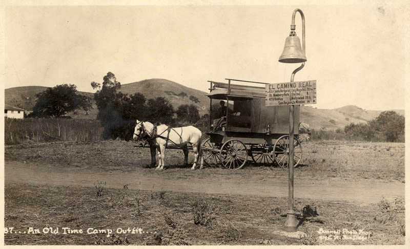 A wagon an an El Camino Real mission bell west of the San Fernando Valley, circa 1920