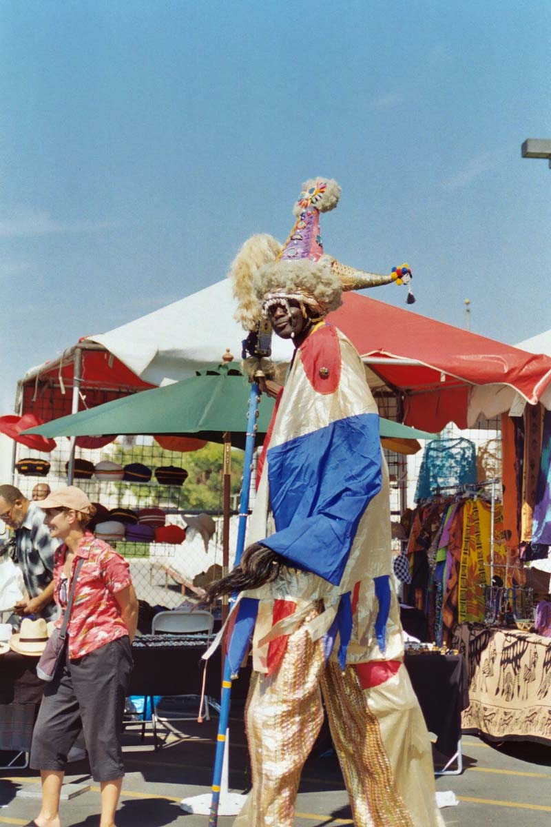 A stilt-walker walks around at a past Watts Towers festival. | Courtesy of Watts Towers Art Center