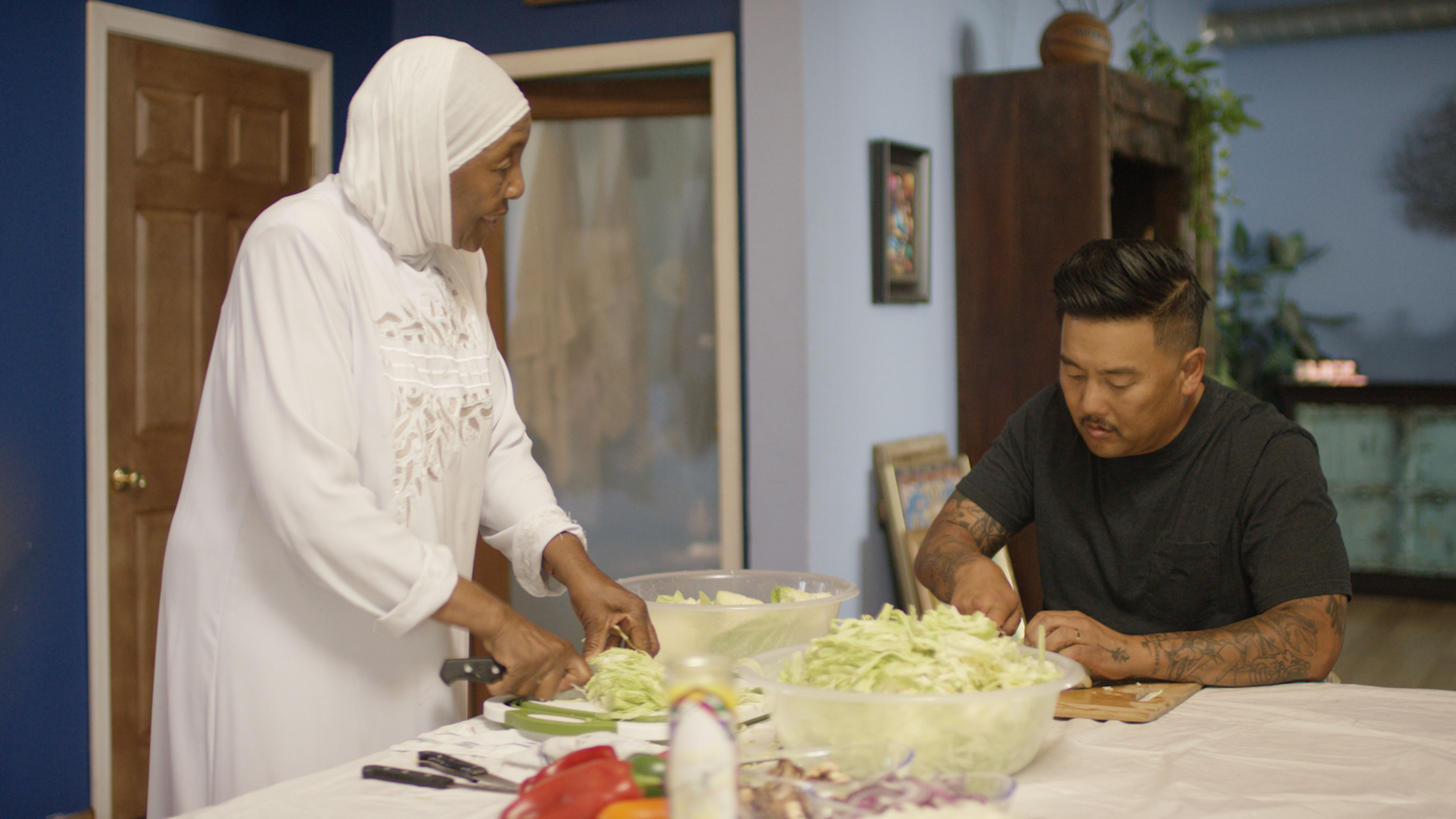 "Led by activist Aqeela Sherrills, Roy visits with Sherrills' mother as she prepares free food for the community in ""Watts""."