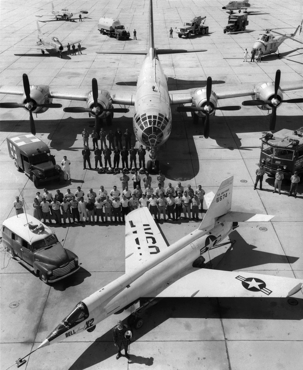 Air Force test pilot Capt. Iven Kincheloe stands in front of the Bell X-2 (46-674) on the ramp at Edwards Air Force Base, California. Behind the X-2 are ground support personnel, the B-50 launch aircraft and crew, chase planes, and support vehicles. |