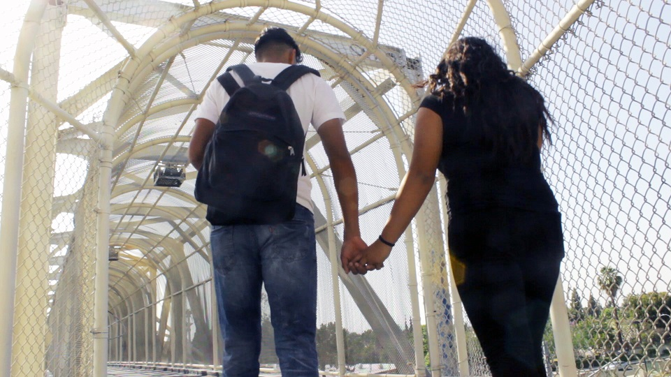Roots|Raices: Young Couple Holding Hands on Bridge